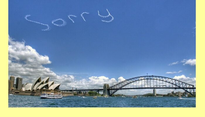 "Blue sky over Sydney harbor with skywriting ""Sorry"""