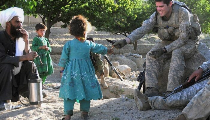 A smiling American soldier reaches out to an Afghan girl